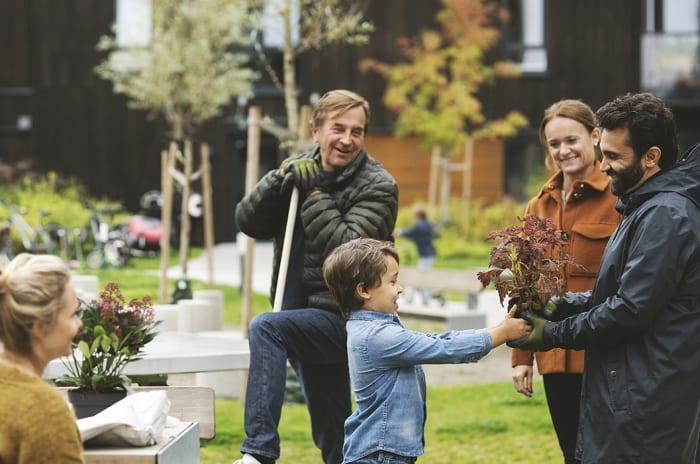 En gutt gir en plante til en mann i OBOS nabolaget