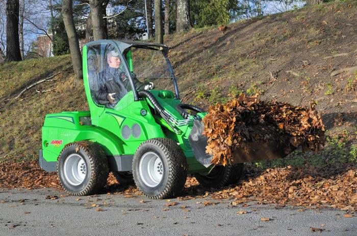 En traktor som løfter vekk løv.