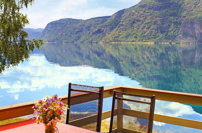 En terrasse med et vann og fjell i bakgrunnen