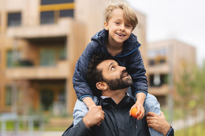 En ung gutt på skuldrene til far