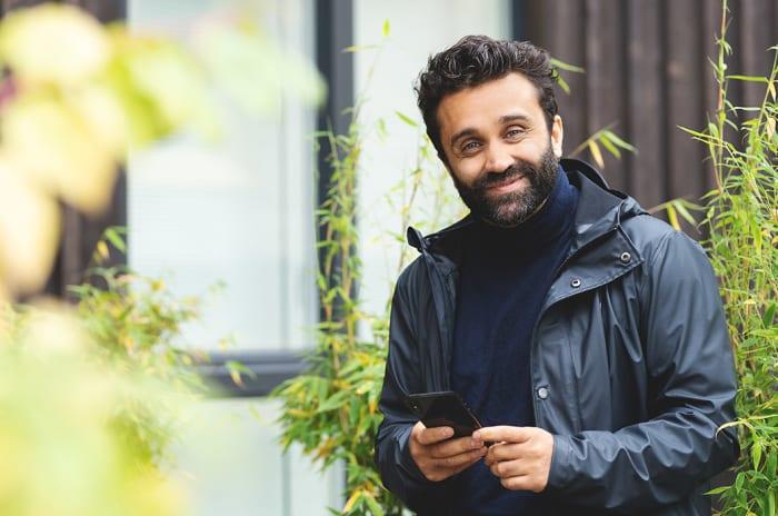 Mann med en mobiltelefon i hendene