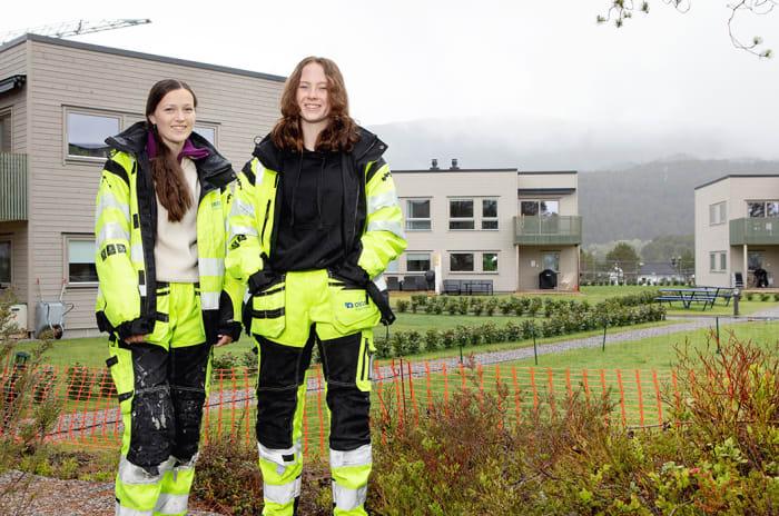 To unge kvinner i tømreruniform foran et boligområde