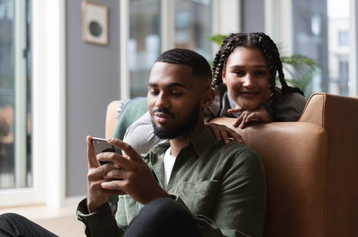 To personer ser på tilbudet av tjenester via mobiltelefon