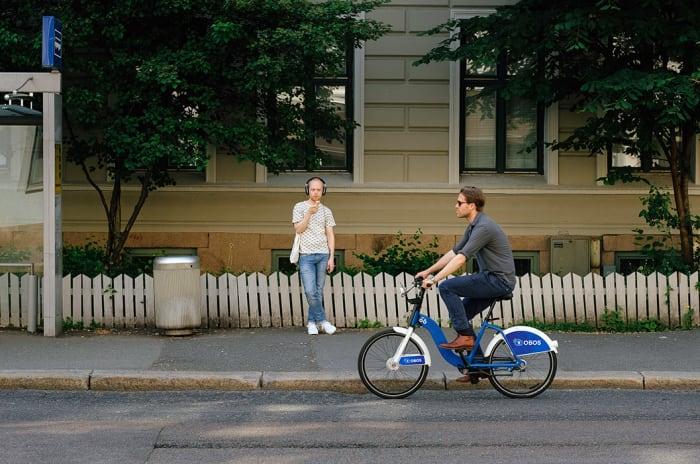 En mann på en bysykkel som sykler forbi en bussholdeplass