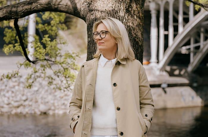 Kvinne med blondt hår lener seg mot et tre.