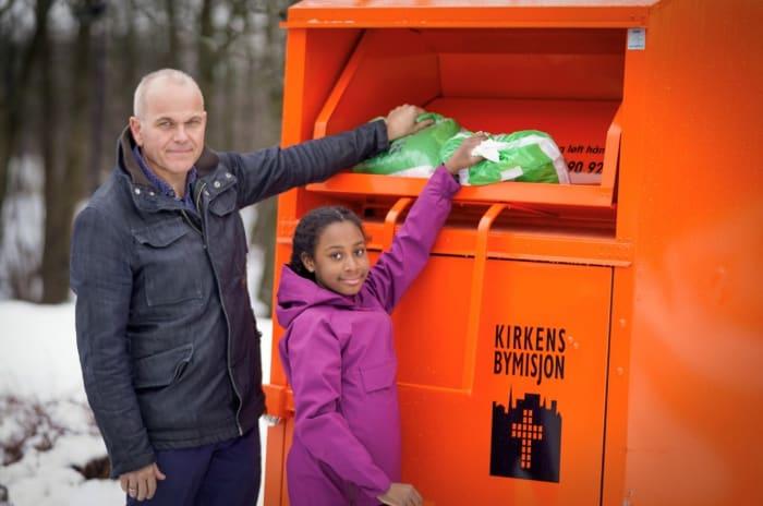 En mann og en jente gir klær i en innsamlingsboks fra Kirkens Bymisjon Foto: Torstein Ihle
