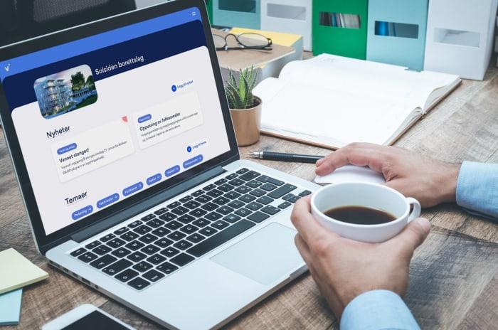 pc med Vibbo på skjermen og to hender som holder en kaffekopp.