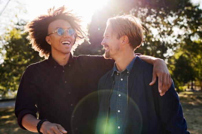 To menn i en park med sola i bakgrunn