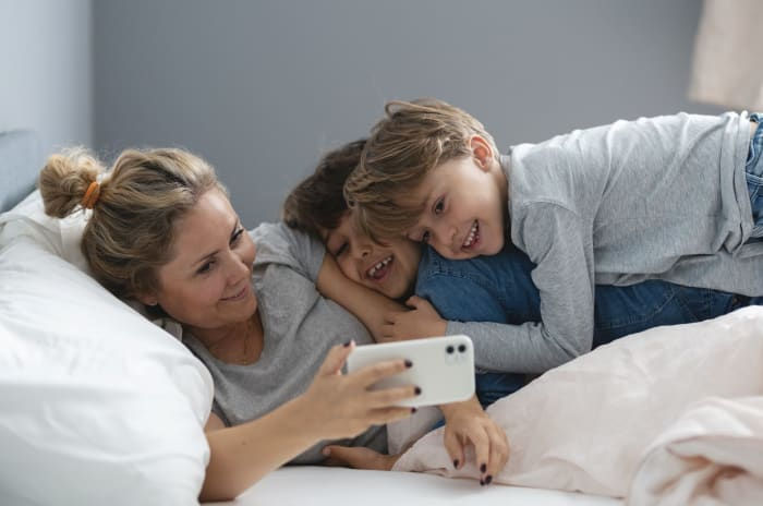 familj i säng med mobiltelefon