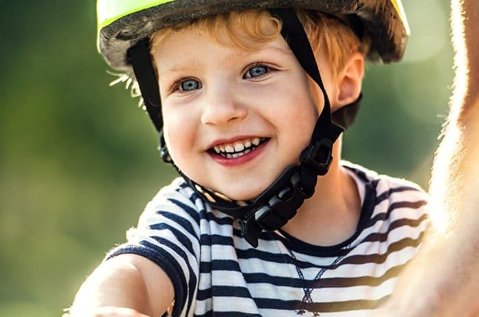 En liten gutt smiler på en sykkel.