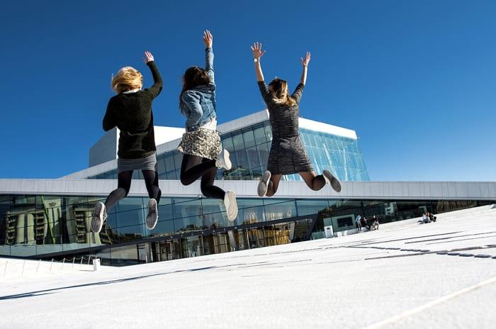 Tre mennesker som hopper foran Operaen