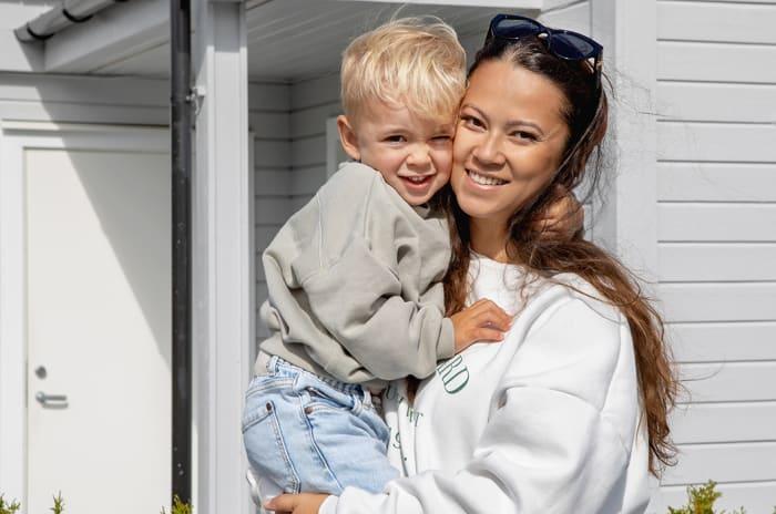 Mor holder sin sønn foran et hvitt hus