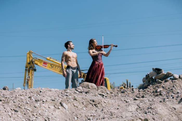 En danser og en dame som spiller fiolin på en byggeplass