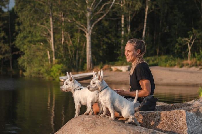 kvinna och två hundar sitter vid sjö