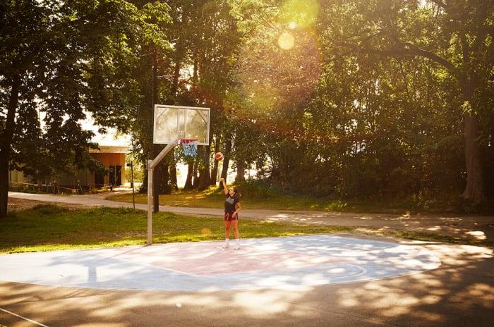 Foto av en person med en basketball på en basketbane.