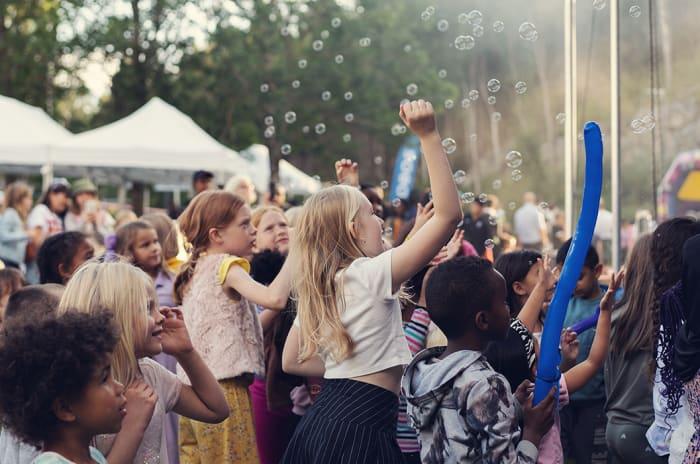 Barn i publikum danser foran scenen på en konsert.