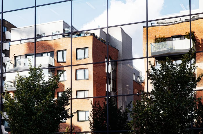 Foto av boligbygg i Kværnerbyen som speiler seg i vinduer.