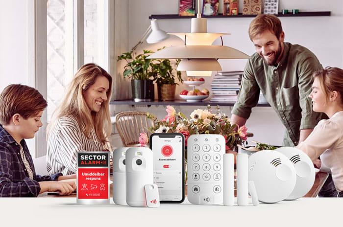 Familie sitter rundt middagsbord med Sector Alarm Produkter