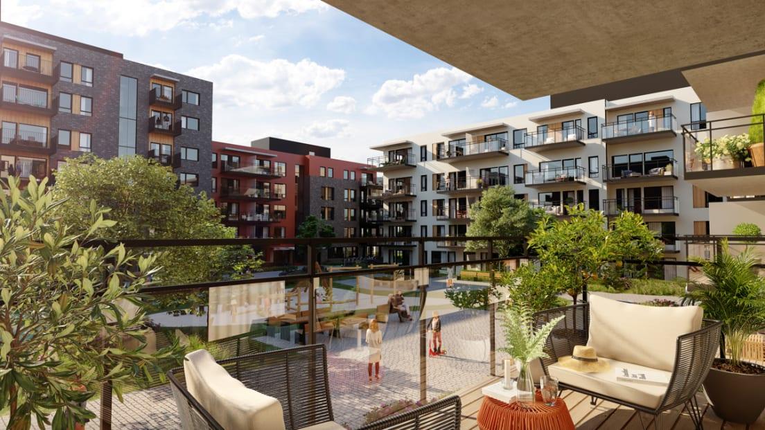 Utsikt fra balkong mot boligblokker og rekreasjonsområder
