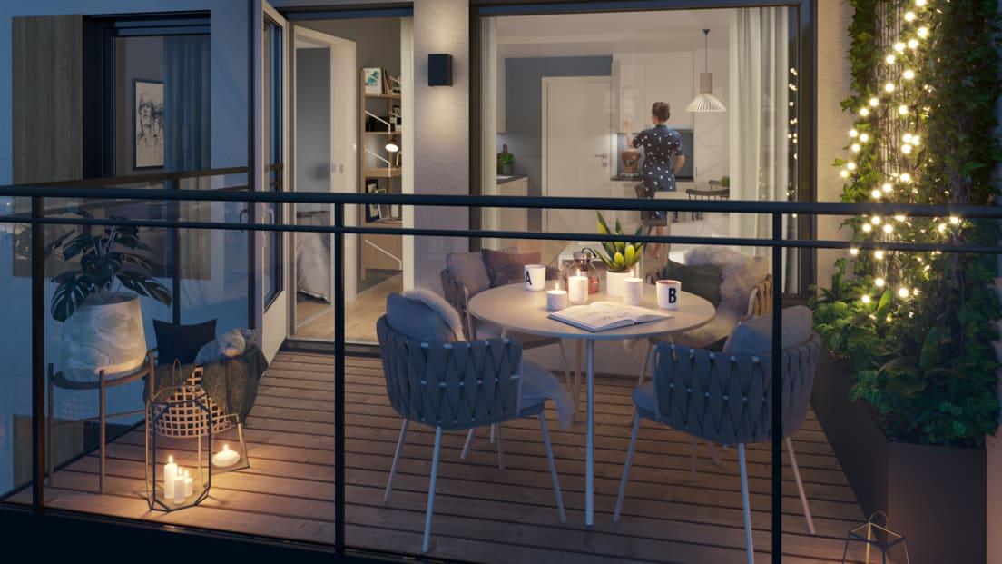 Kveldsbilde av balkong med bord og stoler og en kvinne inne på kjøkkenet