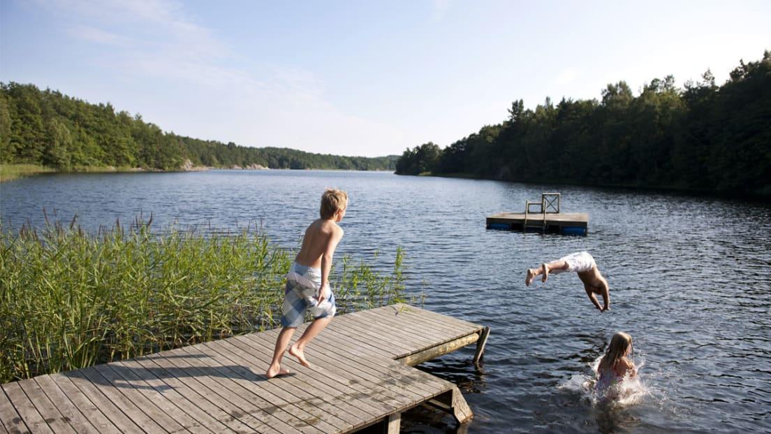 Barn som bader fra brygge