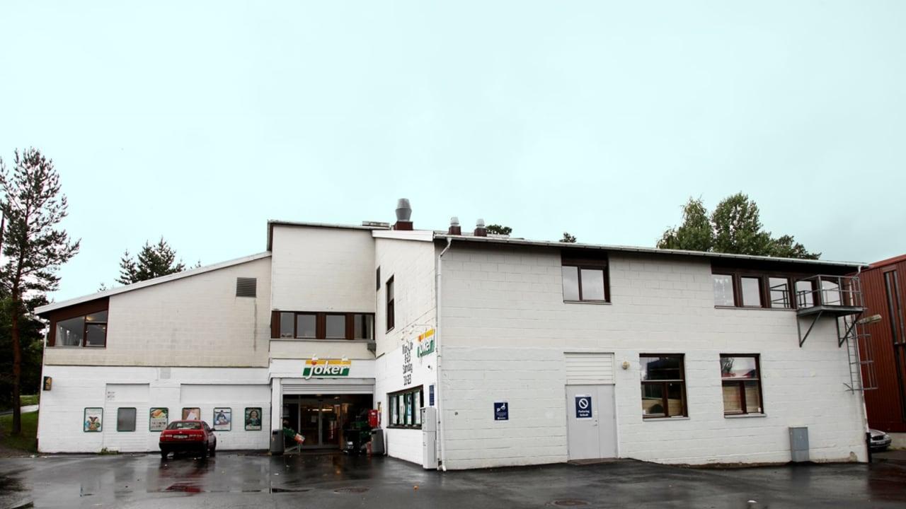Bilde av Hallagerbakken. Butikklokaler i to etasjer. Hvit murfasade.