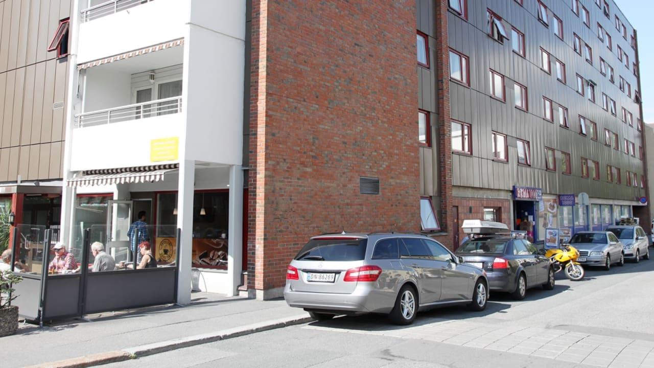 Bilde av Mogata 5. Høyblogg med rød mursteinsfasade på siden og hvite balkonger foran.