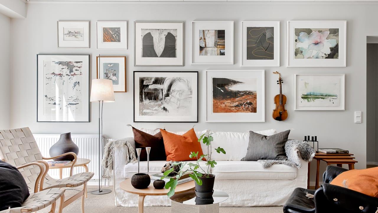 en vit soffa framför en tavelvägg i ett vardagsrum