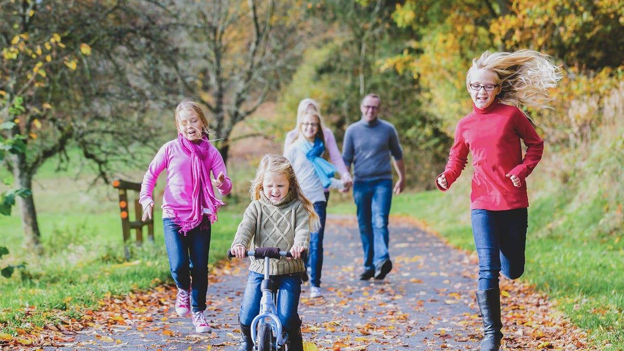 En kvinna och en man ute på höstpromenad med tre barn varav en cyklar