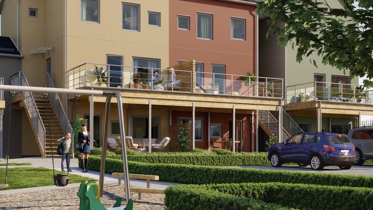 lägenhetskomplex i trä med trädäck och gräsmatta