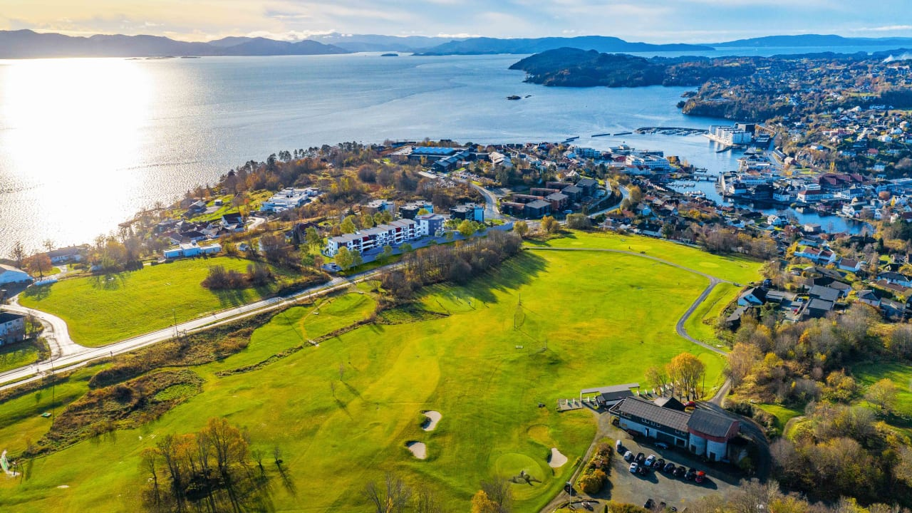 Oversiktsfoto av Solstrandvegen-området, golfbane og fjorden.