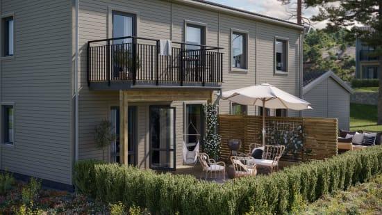 grått parhus i trä med terrass