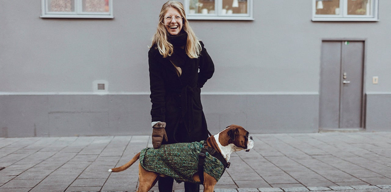Foto av en smilende dame i svart kåpe og en brun hund på fortauet foran en grå blokk.