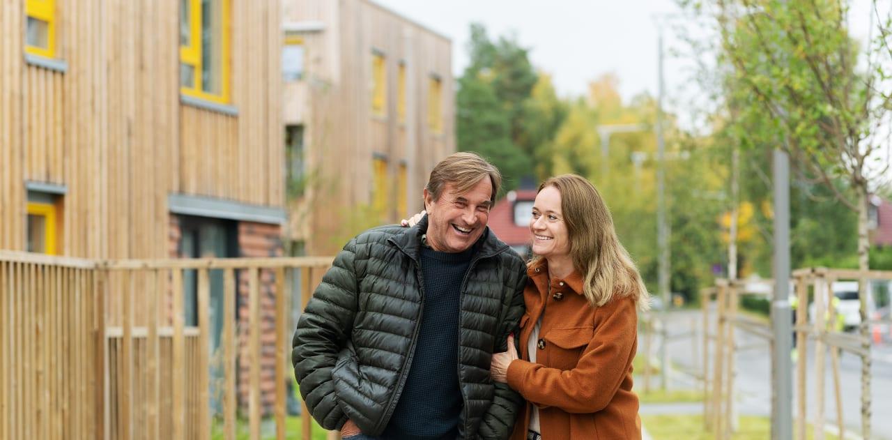 Smilende mann og kvinne holder hender.
