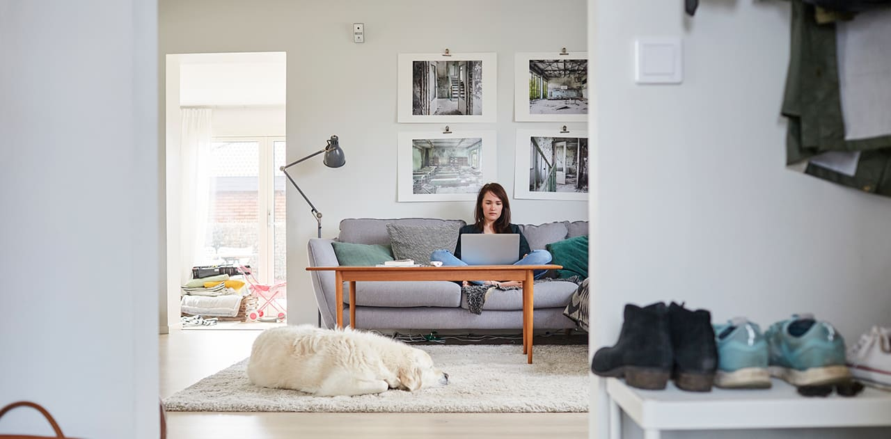 Ung kvinne som sitter i sofaen med PC-en på fanget.