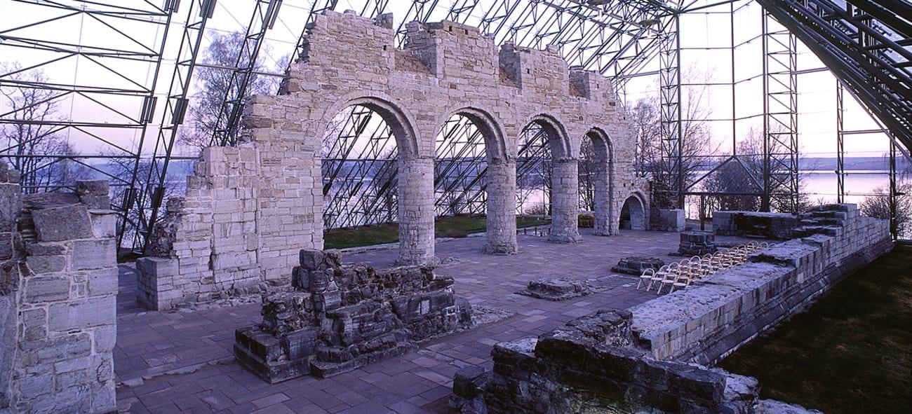 En søyleruin i mur, med et overbygg i stål og glass.