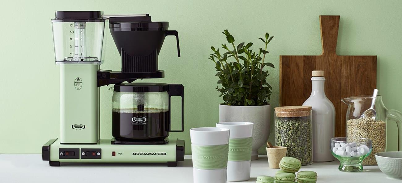Kjøkkenbenk med mintgrønn kaffetrakter og detaljer, mot en mintgrønn vegg