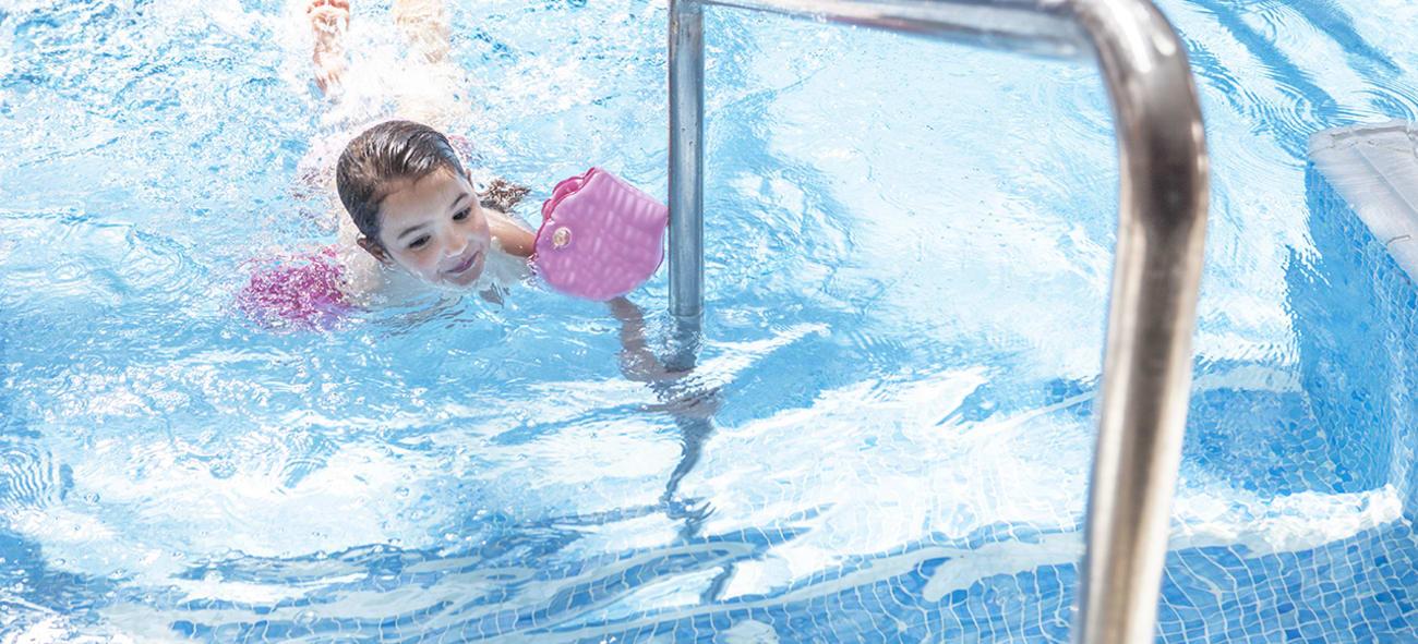 En liten jente med rosa baderinger koser seg i bassenget.