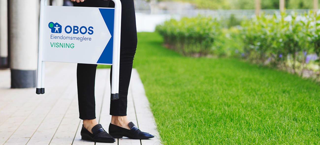 En dame i mørke bukser og flate sorte sko holder et visning-skilt fra OBOS Eiendomsmeglere.