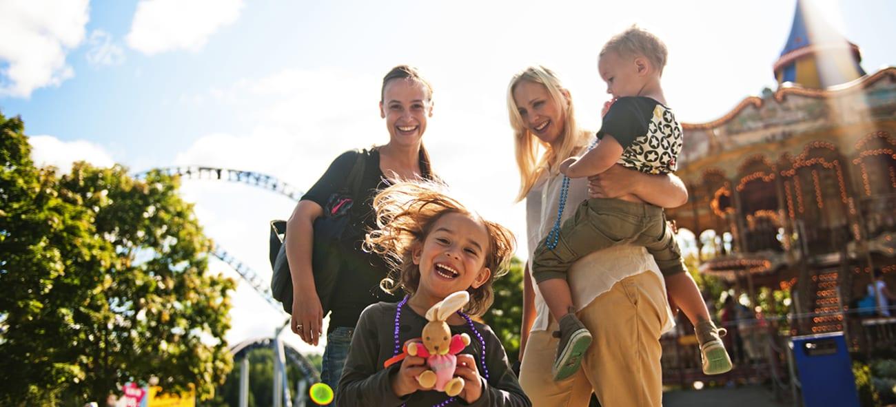 Foreldre og barn smiler og koser seg på TusenFryd