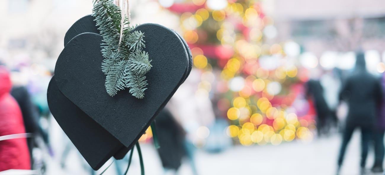 Julepynt i forgrunnen og lysene fra et juletre i bakgrunnen