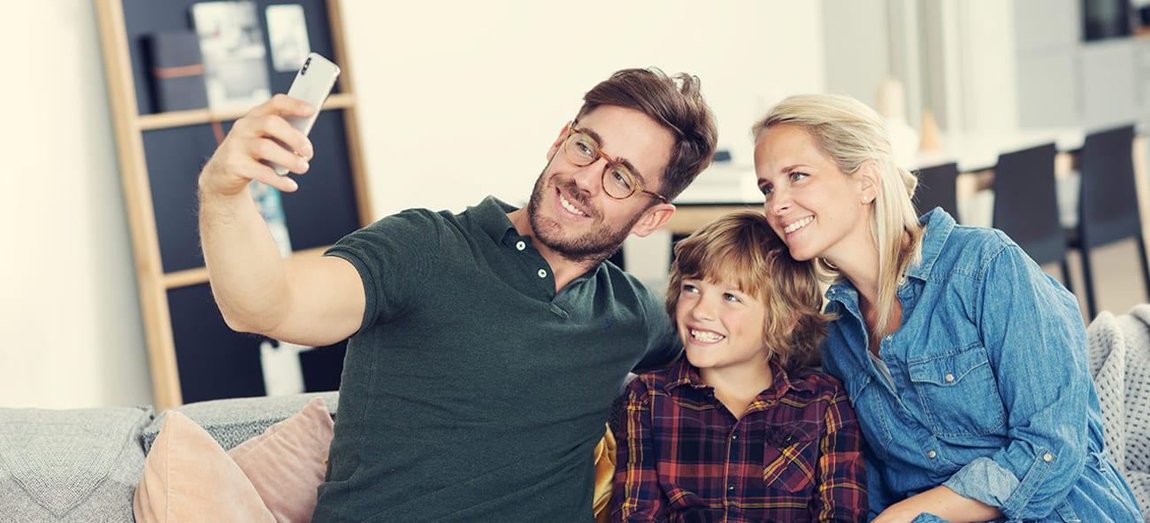 Bilde av en familie på tre som tar en selfie.