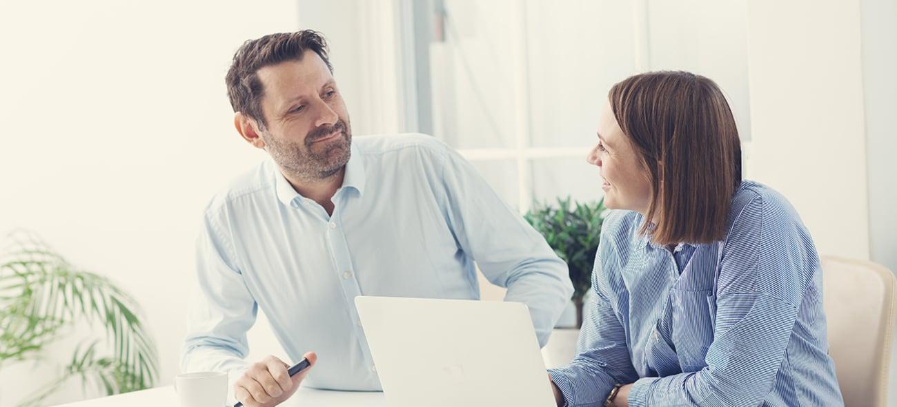 Illustrasjonsbilde av banktjenester. Bildet viser to personer foran et skrivebord med PC.