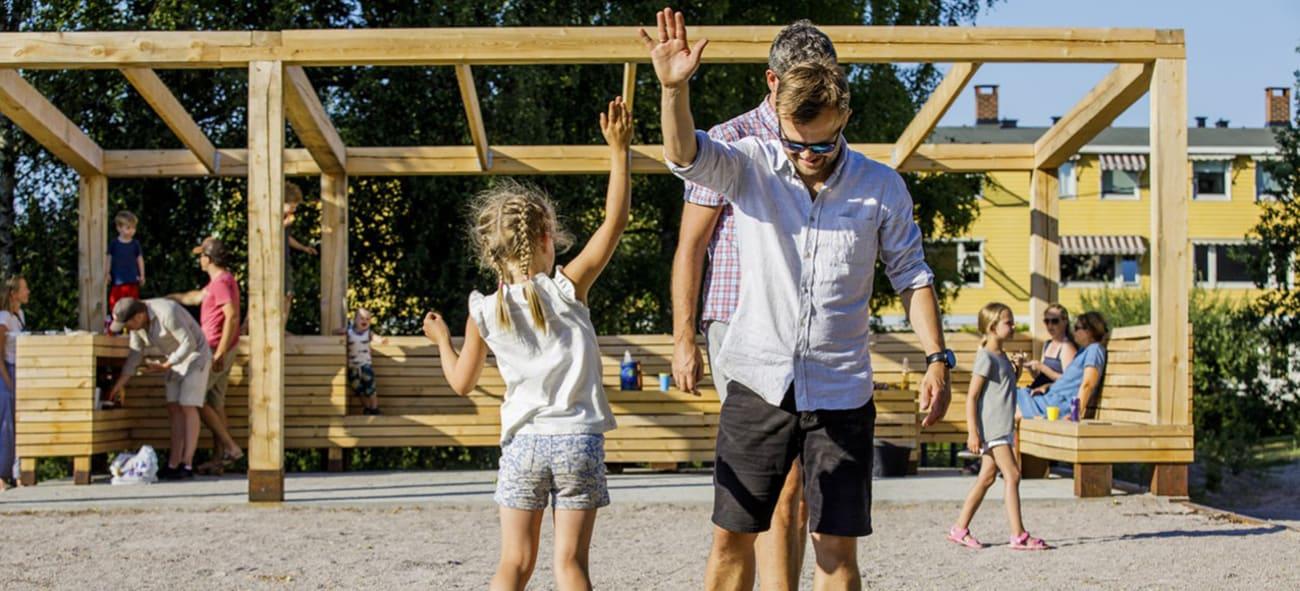 Pappa og datter som spiller boccia på en hyggelig lekeplass