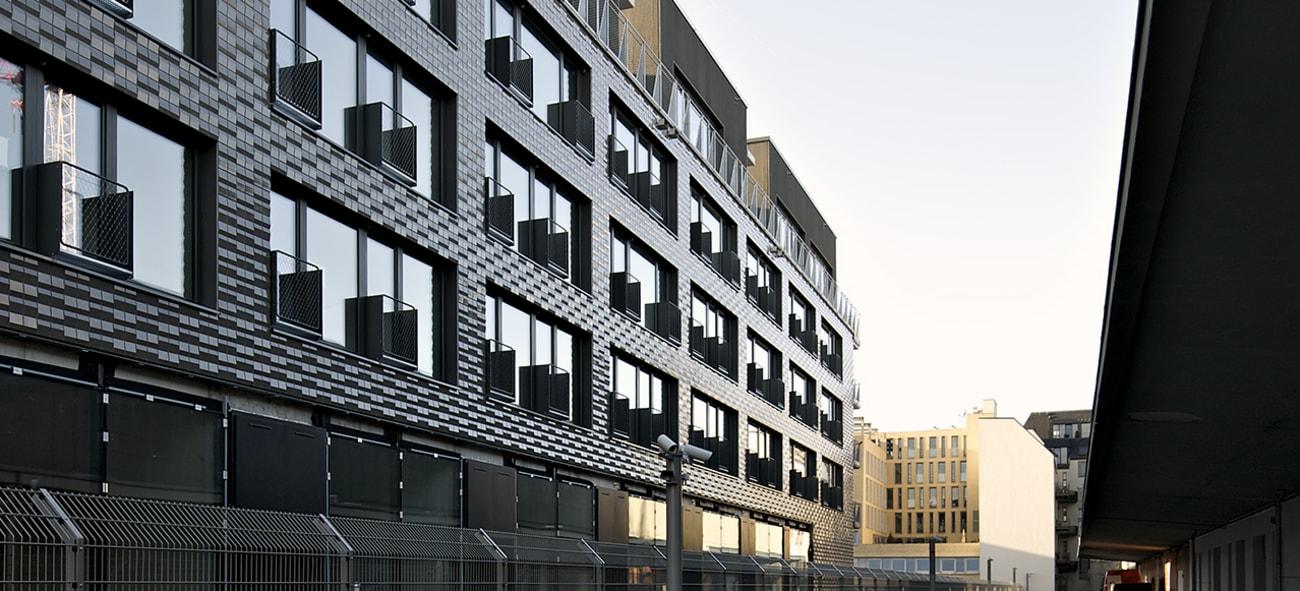Bilde av en offentlig mørk bygning med et høyt gjerde rundt