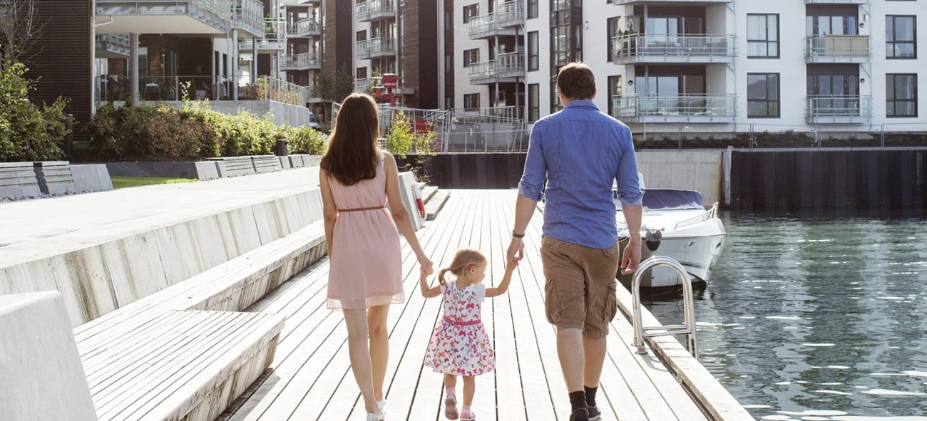 Mor, datter og far spaserer på en brygge