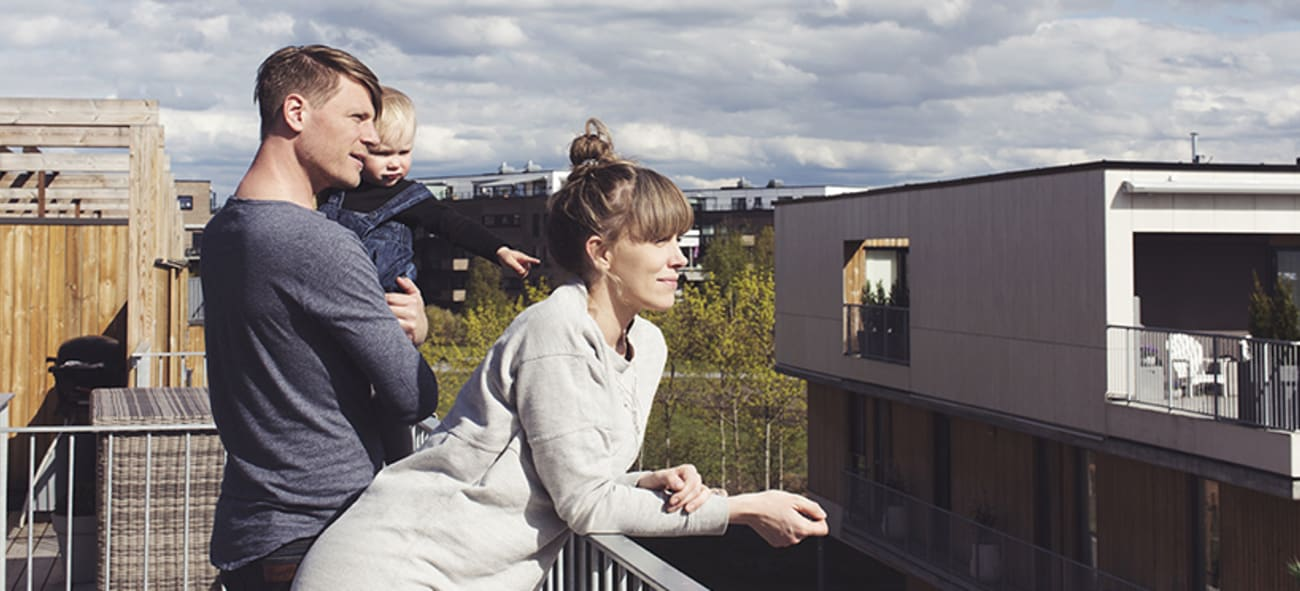 Ungt par med barn står og speider på balkong