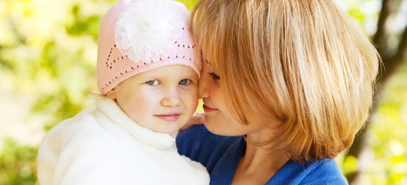 Kvinne som holder barn med rosa lue