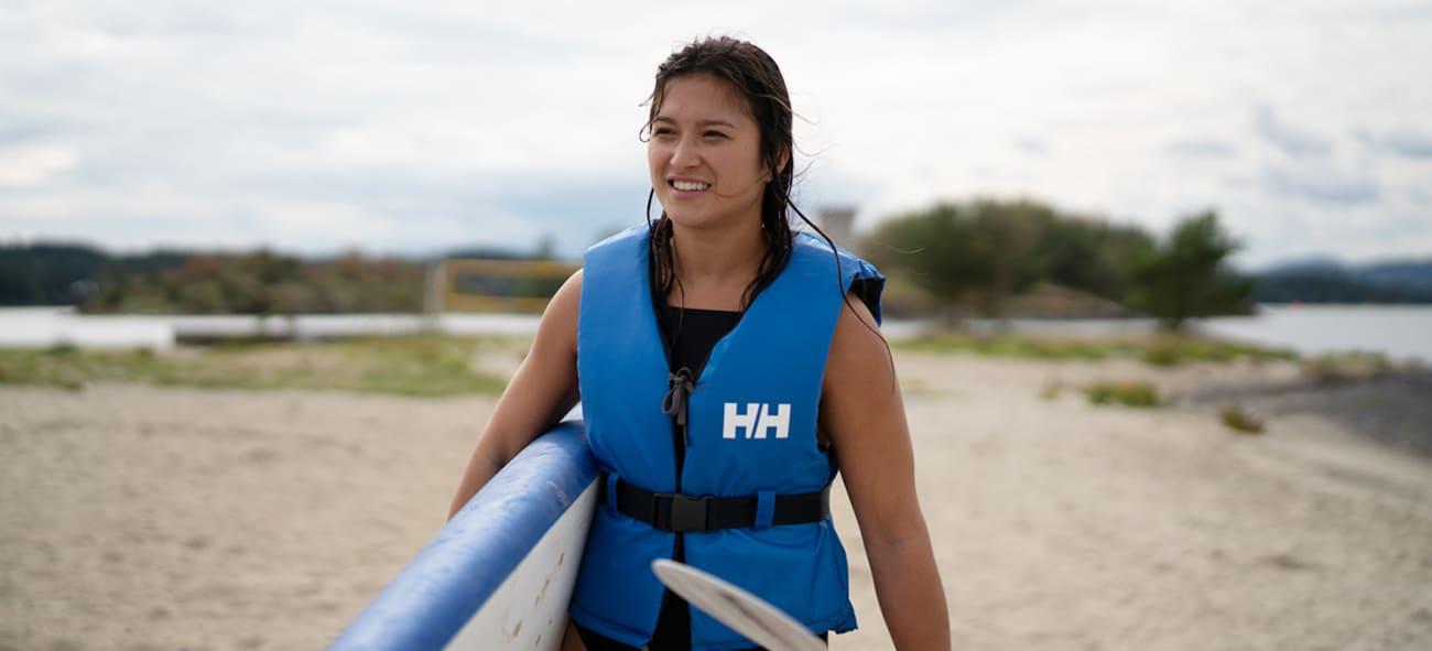 Bilde av kvinne som bærer vindsurfebrett på stranden