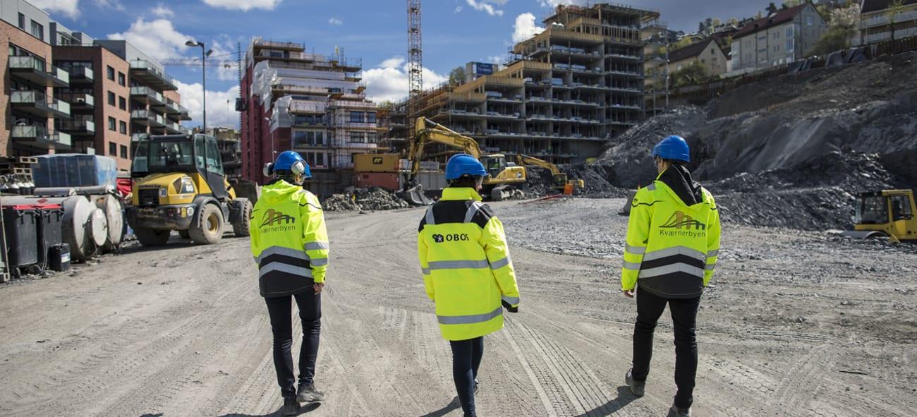 Mennesker med hjelm og OBOS-jakker på en byggeplass